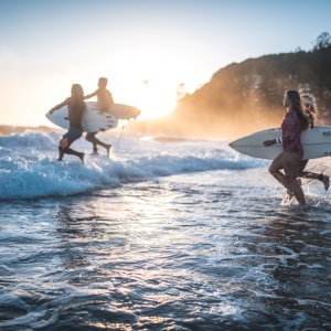AU.Gold_Coast_Surfen Der Blick auf vier Surfer, die mit ihren Surfbrettern in den Ozean laufen.