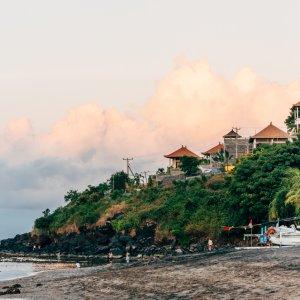 Bali.Amed.Sonnenuntergang Strand in Amed bei Sonnenuntergang, Hintergrund kleine Häuser auf grünem Felshang, Bali