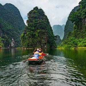 VN.Ninh_Binh_Bootstour Der Blick von hinten auf ein von Personen besetztes Boot inmitten eines Flusses umgeben von grünen Kalkfelsen.