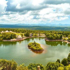 """MU.Westkueste.Tempel Blick auf die grüne Umgebung des Grand Bassin Sees und den dort liegenden Tempel """"Ganga Talao"""""""