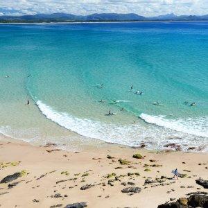 AU.Byron_Bay_Cape_Byron_Wategos_Beach Der Blick auf Wategos Beach mit Menschen im Wasser.