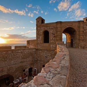 MA.Essaouira.Festung Sonnenuntergang auf den Festungsmauern von Essaouira in Marokko mit Blick zum Fort