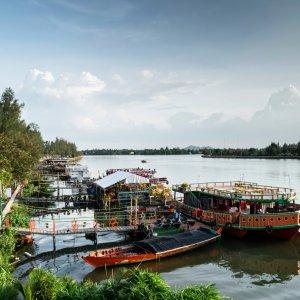 KH.Kampot_Riverside Der Blick auf touristische Restaurantboote und Landschaft am Flussufer in Kampot, Kambodscha.