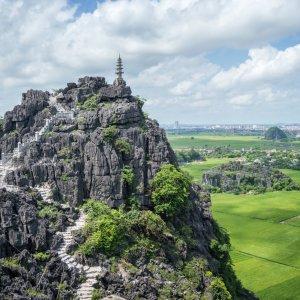 VN.Ninh_Binh_Lying_Dragon_Mountain Der Blick auf einen Kalkfelsen umgeben von grünen Reisfeldern.