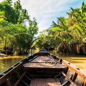 VN.Mekong-Delta Der Blick auf ein Holzboot auf einem Fluss umgeben von Pflanzen.