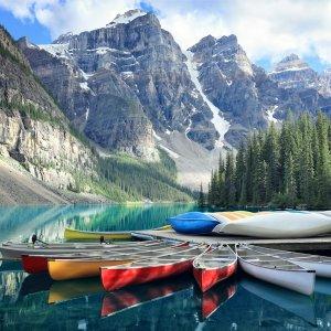 CA.Banff_Nationalpark_Daemmerung Bunte Kanus auf einem See am Fuße der Rocky Mountains im Banff Nationalpark, Kanada
