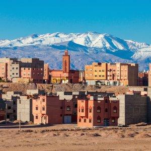 MA.Ouarzazate Panorama Blick auf die Häuser der Stadt Ouarzazate, im Hintergrund die schneebedeckten Berge des Atlas-Gebirges in Marokko