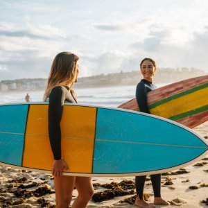 AU.Sydney_Bondi_Beach_Surfer Der Blick auf zwei Surferinnen auf dem Weg ins Wasser.