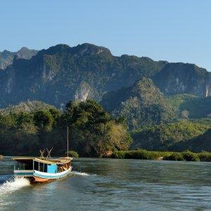 VN.Mekong-Delta_Touristenboot Der Blick auf ein Boot auf dem Mekong Fluss mit grünen Bergen im Hintergrund.