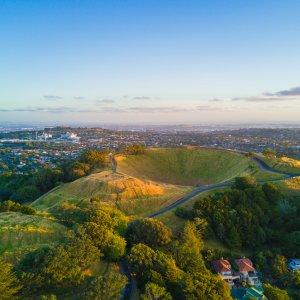 NZ.Auckland_Mount_Eden Der Blick von oben auf den grünen Vulkankrater Mount Eden inmitten der Stadt Auckland.
