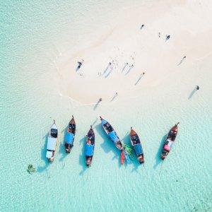 TH.AR.Phuket Boote Blick auf bunte Boote, einen weißen Strand und das türkisblaue Meer aus Vogelperspektive