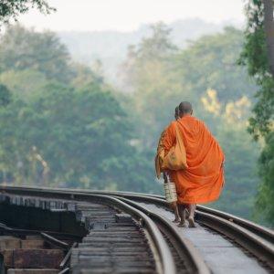 TH.AR.Kanchanaburi Death Railway Ein Mönch, der auf den Gleisen des Death Railways entlang geht