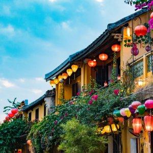 VN.Hoi_An_Lampions Der Blick auf gelbe Häuser mit Lampions und bunte Blumen bedeckt.