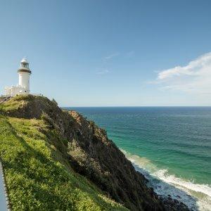 AU.Byron_Bay_Cape_Byron_Light Der Blick auf einen Luchtturm an der Küste.
