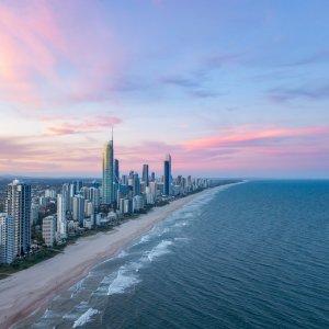 AU.Gold_Coast Der Blick auf die Surfers Paradise Skyline bei Sonnenuntergang mit einem rosa Himmel.