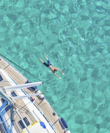MDV.Mann schwimmt neben Yacht