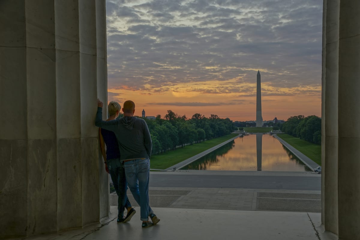 Couple at the Washington Monument and Lincoln Memorial Reflecting Pool at Sunrise in DC USA
