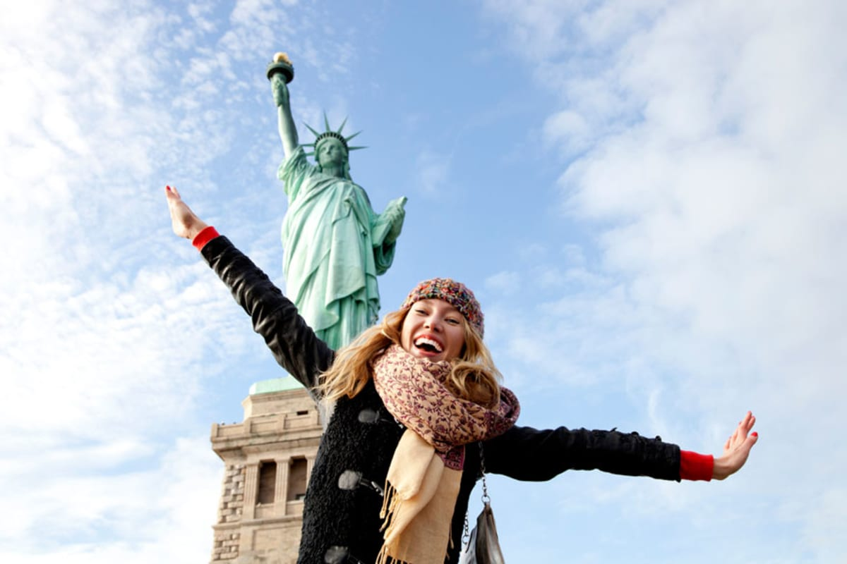 Young woman posing and laughing in front of Statue of Liberty.