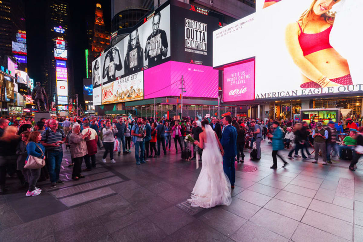 Bride and groom walking in Times Square.