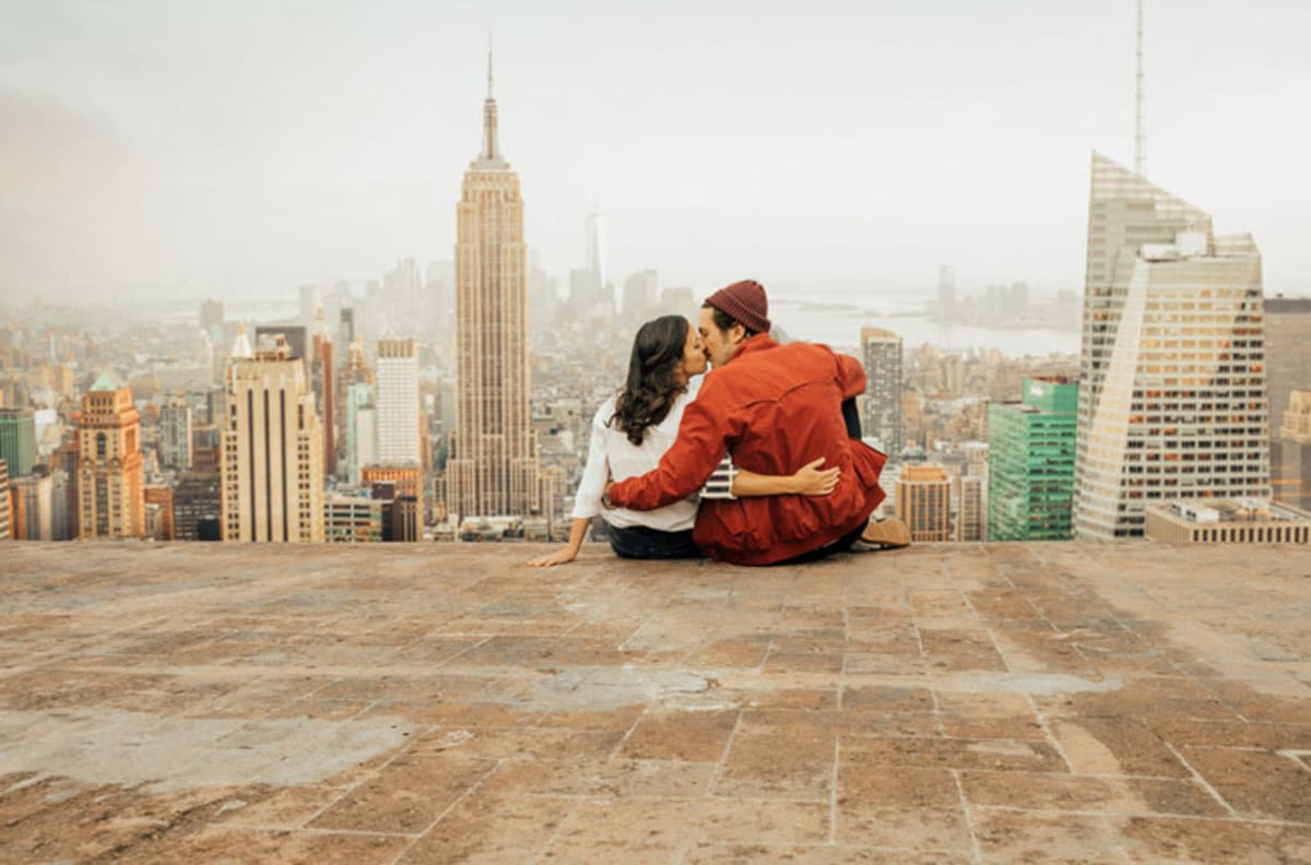 Couple sitting on the floor and kissing with Empire State Building and skyline.