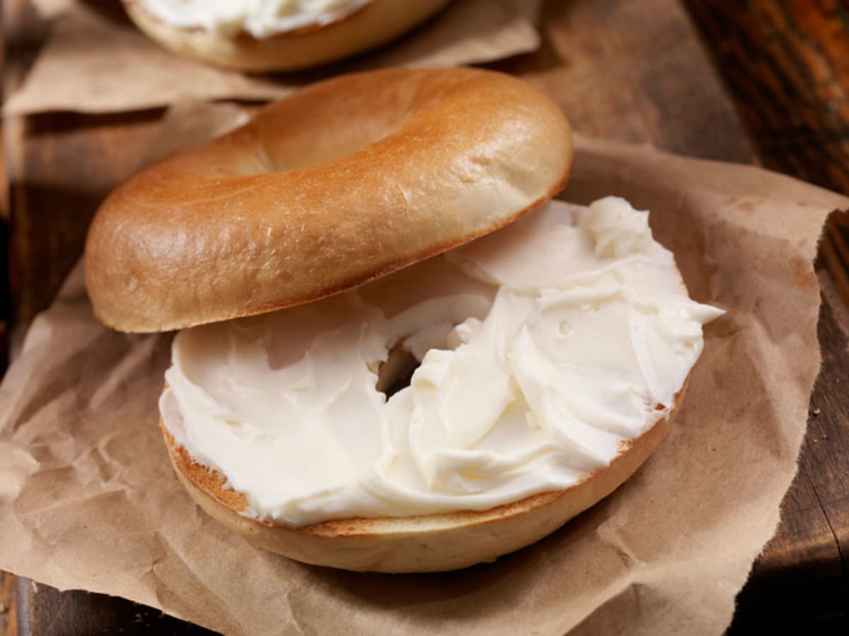White bagel with cream cheese on cardboard wrapping.