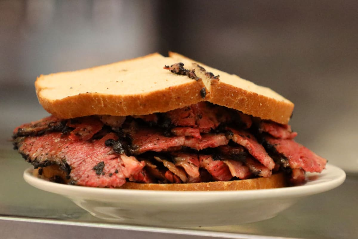 Pastrami sandwich on white plate.