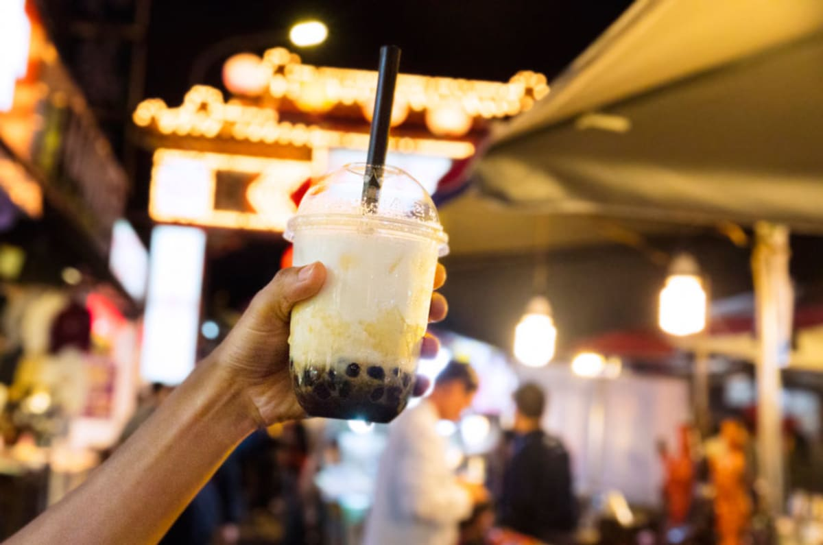Person holding cup with bubble tea against city background.