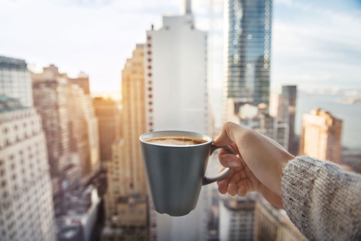 Woman holding cup of coffee in front of Manhattan window.