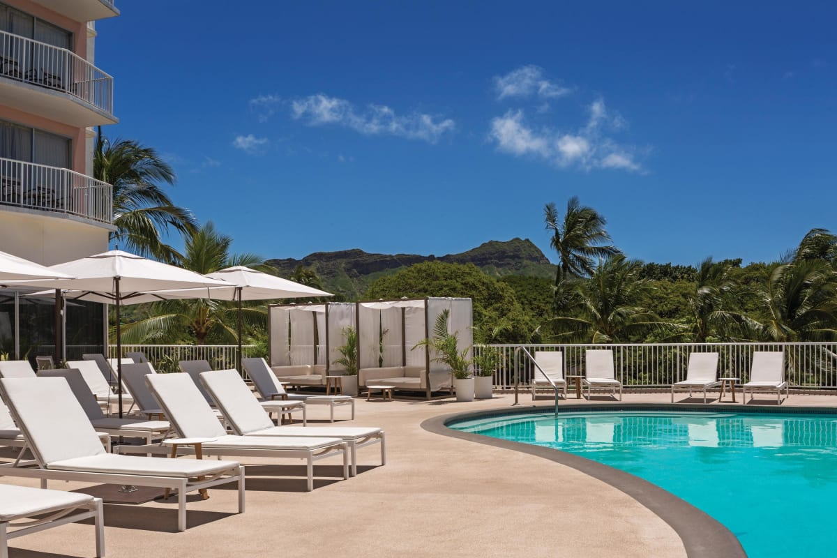 Outdoor view of Diamond Head in background and pool with pool loungers in foreground