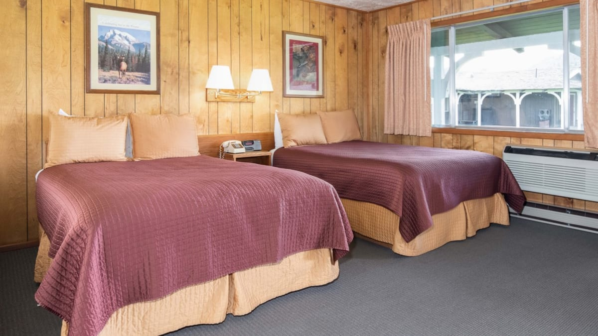 room with wood paneling and two beds