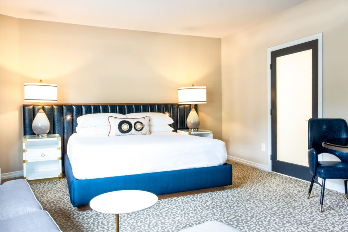 Studio King Suite with white bed and blue accents