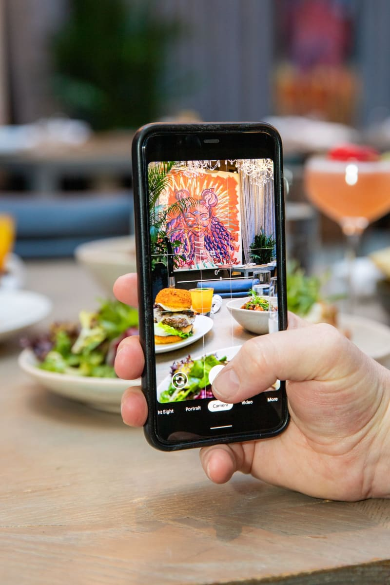 Person taking picture of restaraunt on iphone