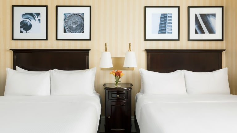 Hotel Whitcomb Double beds and two paintings placed on each headboard. A table with lamps placed between the two beds.
