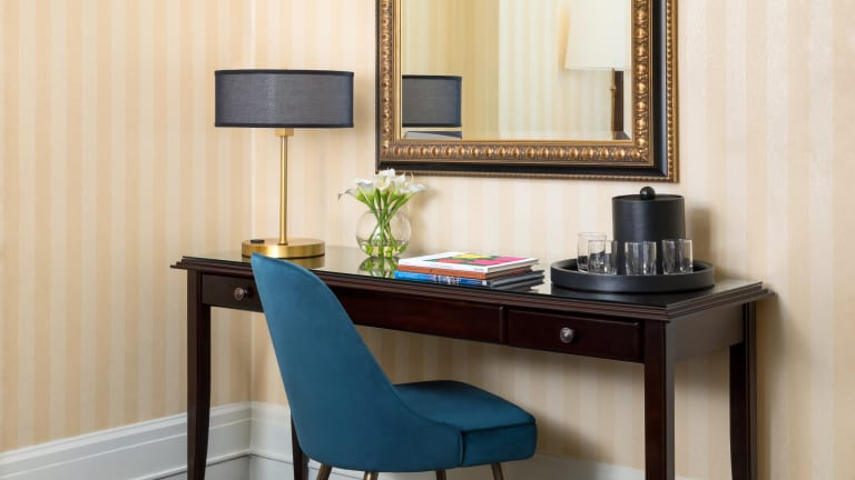 Hotel Whitcomb Room. Table with mirror on top. Lamp, flowers in a vase, water container with glasses in tray and books placed on the desk. And a blue chair placed in front of it.