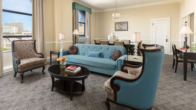 Hotel Whitcomb Suite, living room with sofa and dining table along with 2 windows