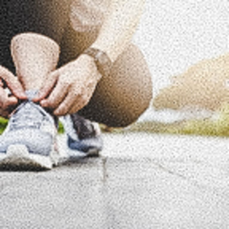 young-woman-tying-running-shoes