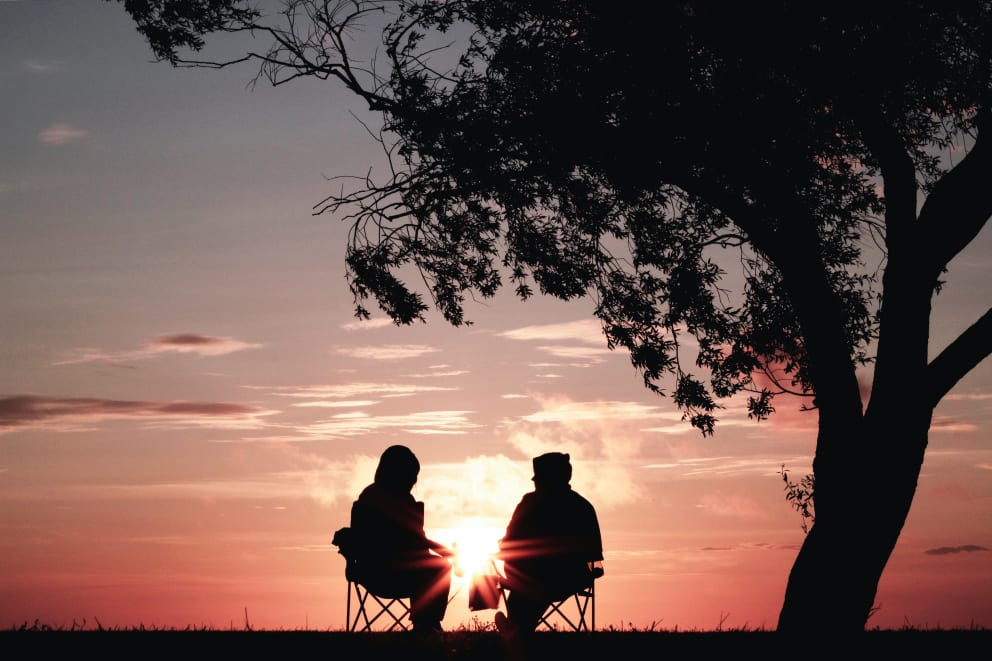 Man and woman watching sunset on lawn chairs