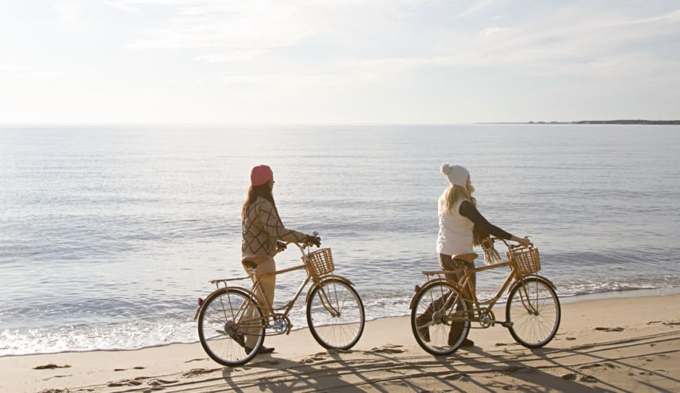 women riding bikes on the beach