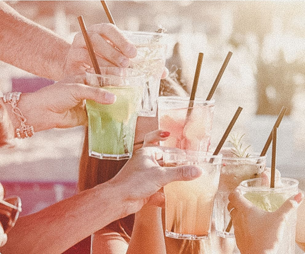 group of people toasting fruity drinks