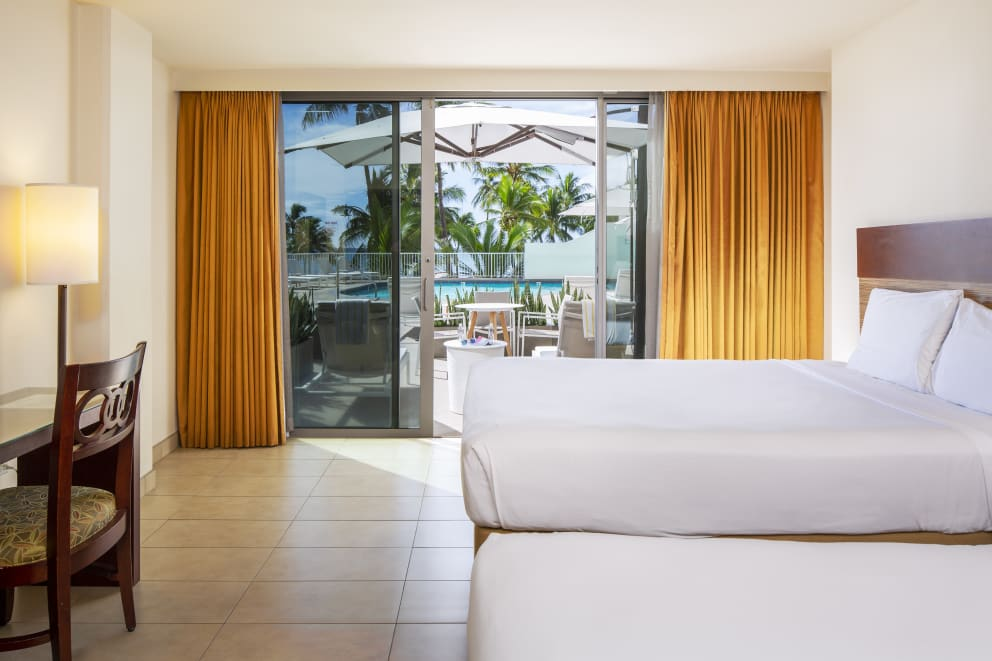 Poolside room with tile flooring and view of pool from lanai