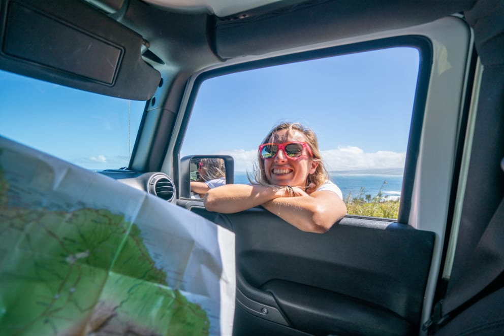 young woman outside car looks at map for directions in hawaii