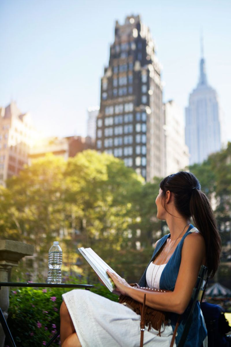 woman-reading-book-in-park-near-empire-state-building