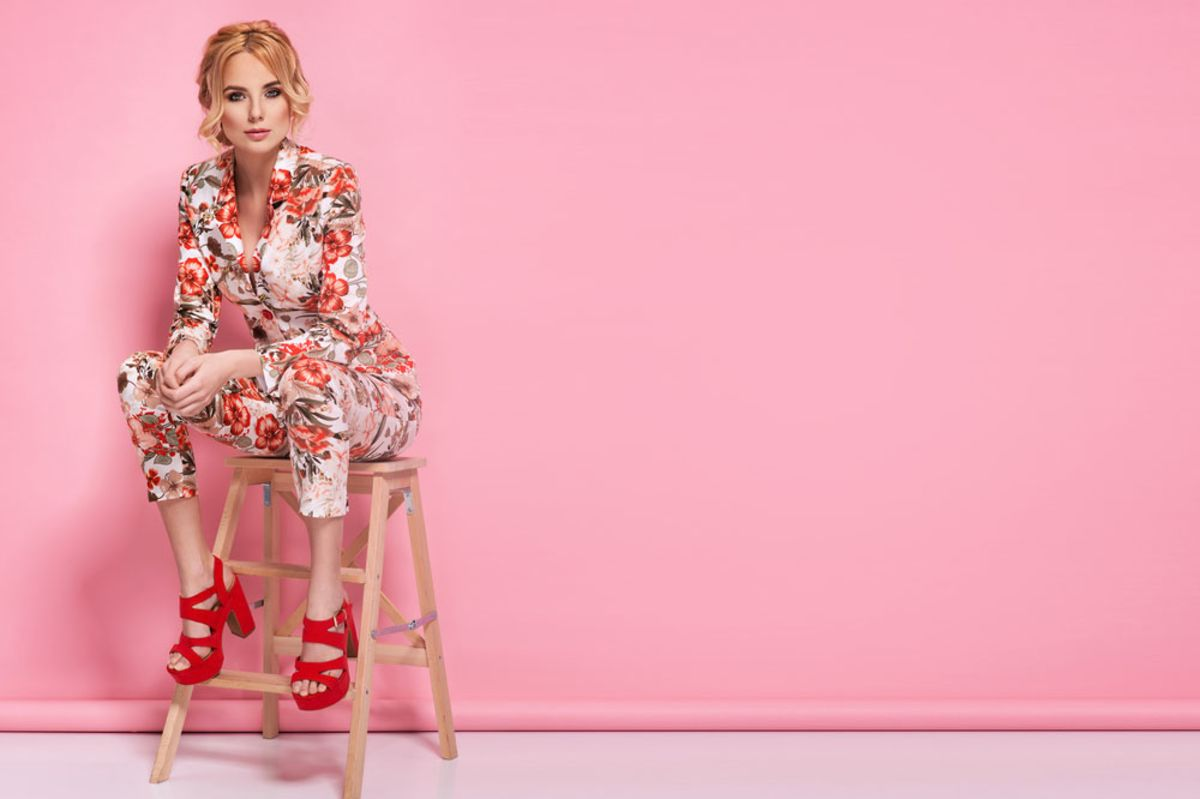 woman-wearing-flowered-suit-sitting-in-front-of-pink-background