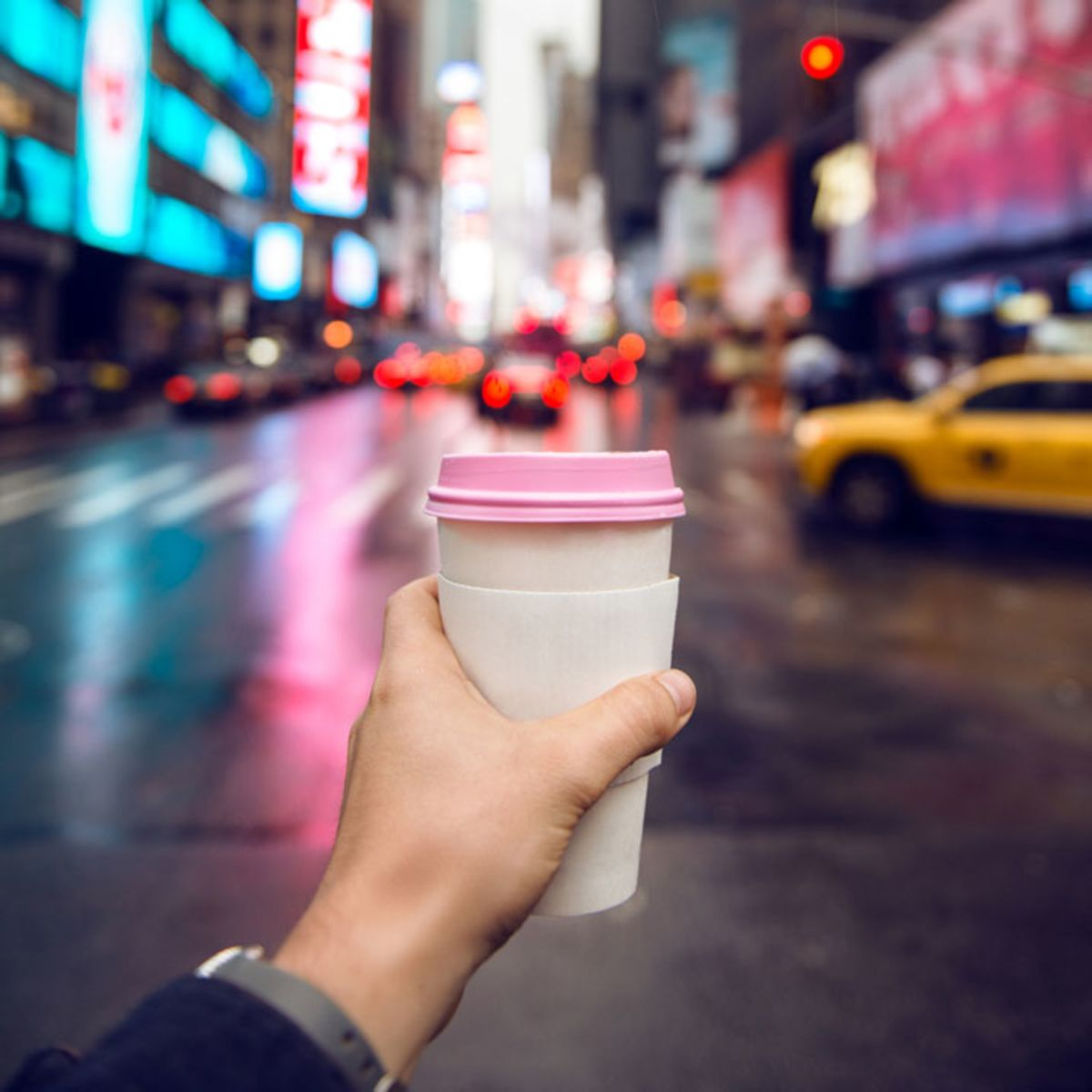 man-holding-disposable-coffee-in-front-of-times-square