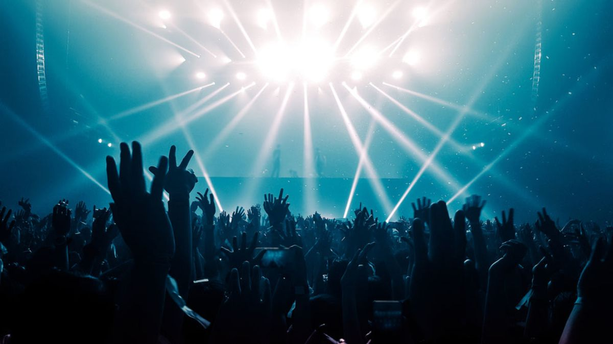silhouette-of-hands-raised-in-a-nightclub-with-lights-in-background