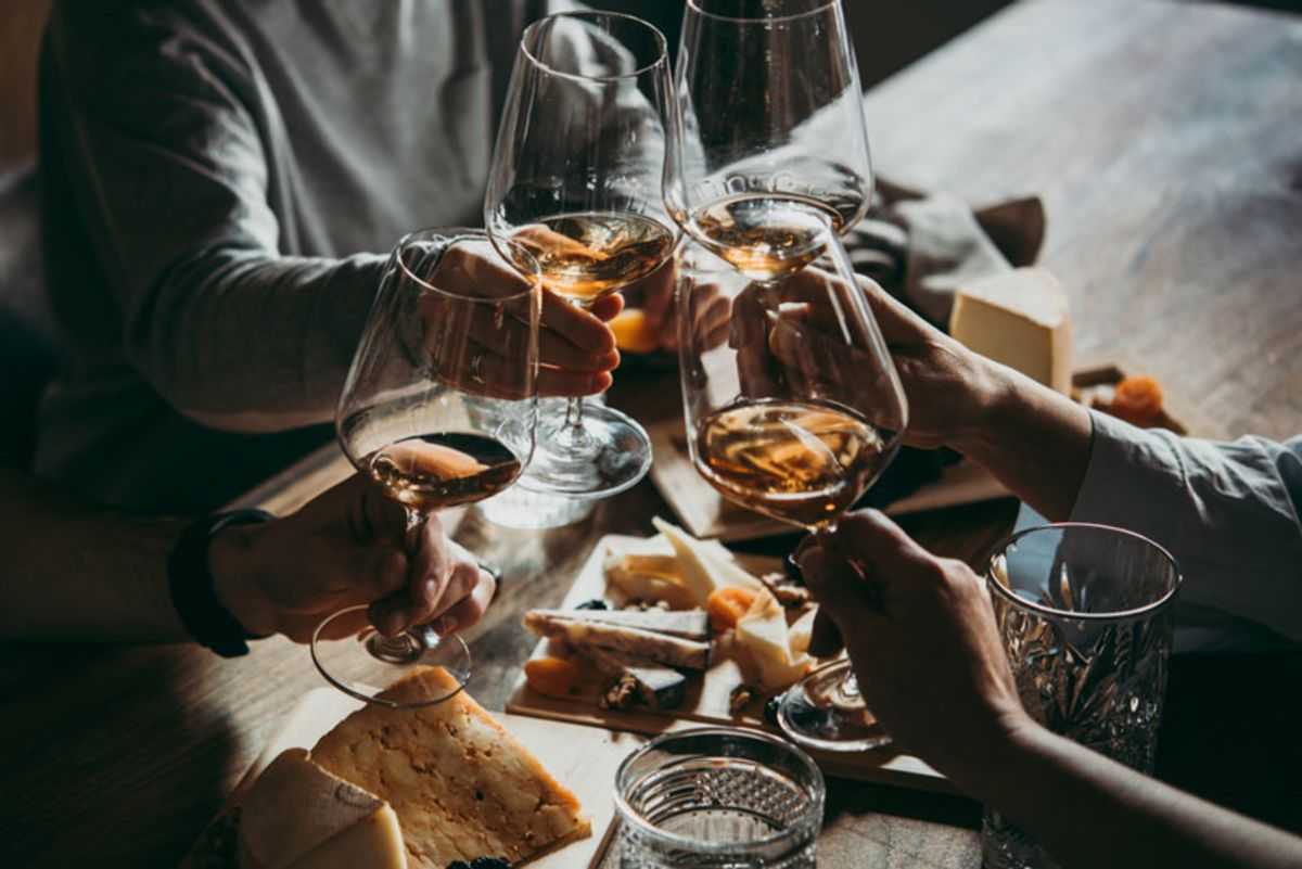 group-of-friends-cheering-with-wine-and-cheese-plates