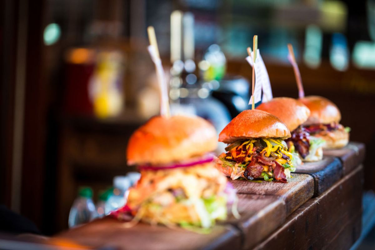 row-of-craft-burgers-in-wooden-counter