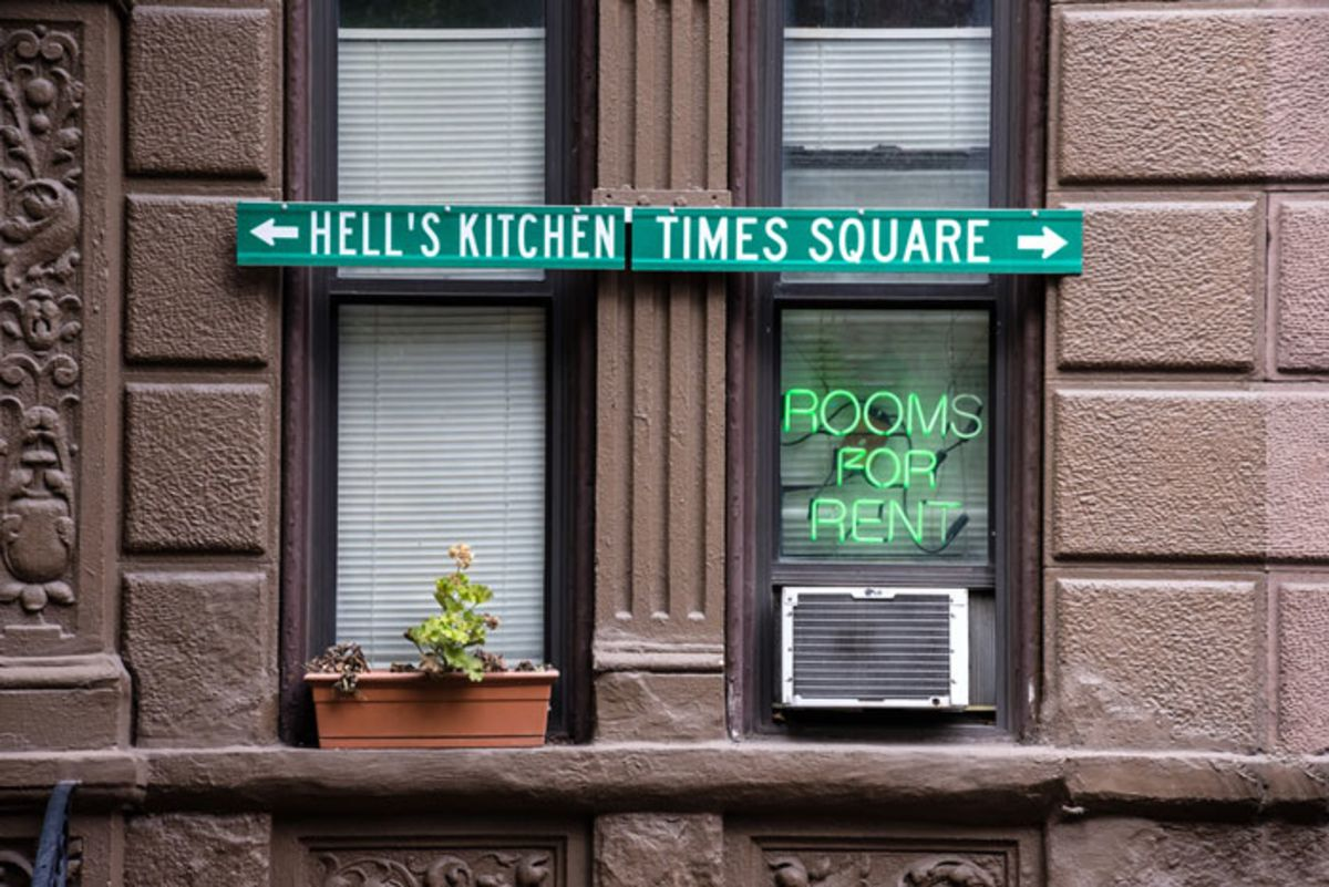 stone-apartment-building-with-signs-pointing-to-hells-kitchen-and-times-square