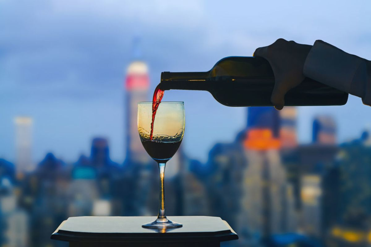 person-pouring-red-wine-into-glass-with-nyc-skyline-in-background