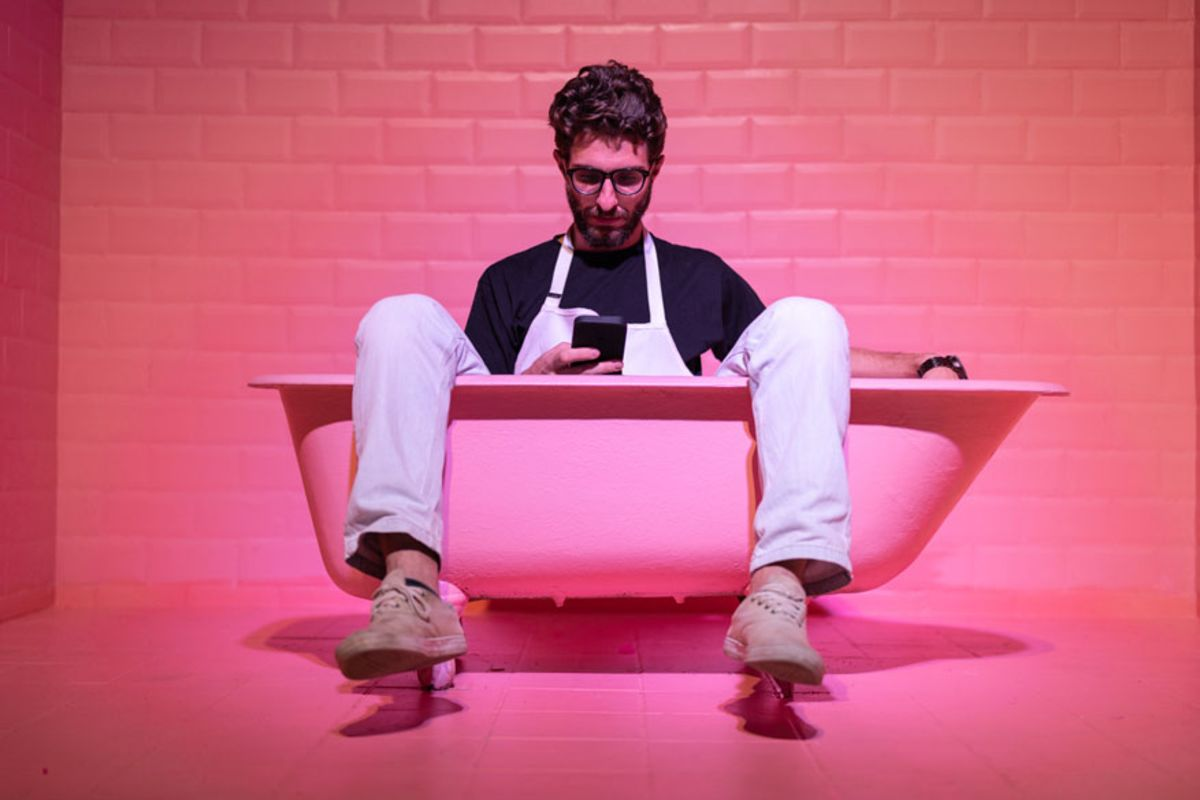young-man-sitting-in-pink-bathtub-looking-at-his-cellphone